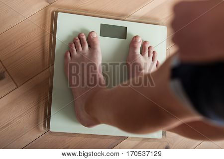 Young teenager weighing himself on a scale in the bathroom in his bare feet to check his weight gain or loss high angle view on a wooden floor stock photo