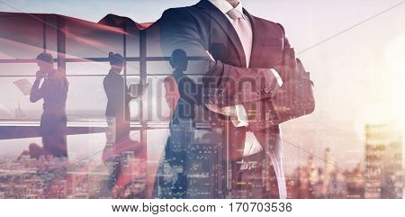 superhero businessman looking at city skyline at sunset. the concept of success, leadership and vict