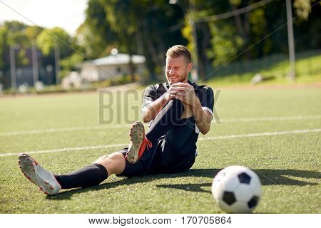 sport, football training, sports injury and people - injured soccer player with ball on field stock photo