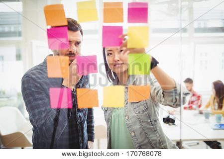 Creative business people looking at multi colored sticky notes on glass in meeting room at creative