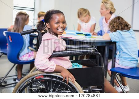Disabled schoolgirl smiling in classroom at school stock photo