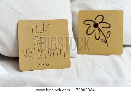 closeup of a brown paper note with the text feliz san valentin, happy valentines day written in Spanish and a flower drawn in another note, on the white sheets of an undone bed stock photo