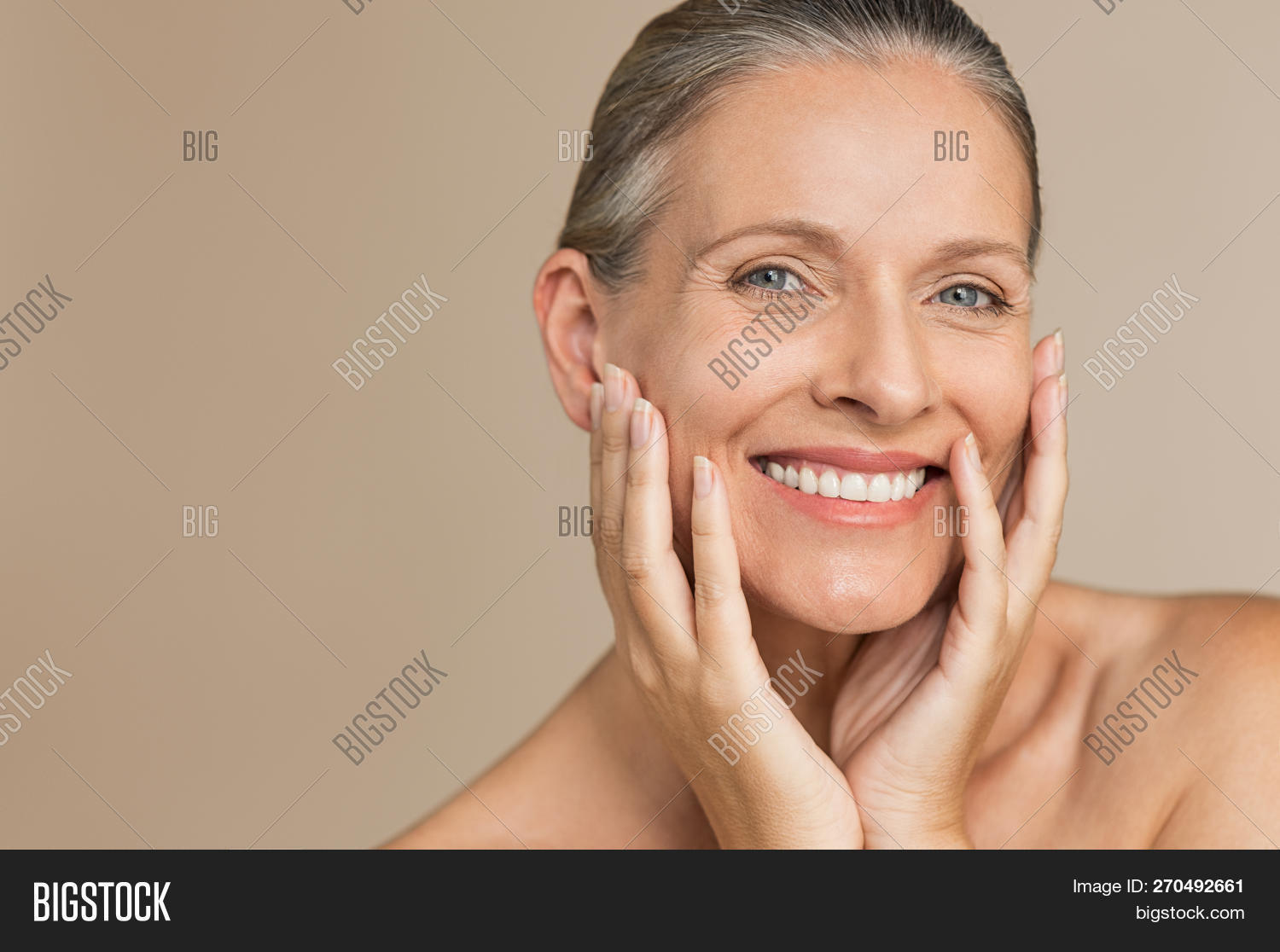 Beauty portrait of mature woman smiling with hand on face. Closeup face of happy senior woman feelin
