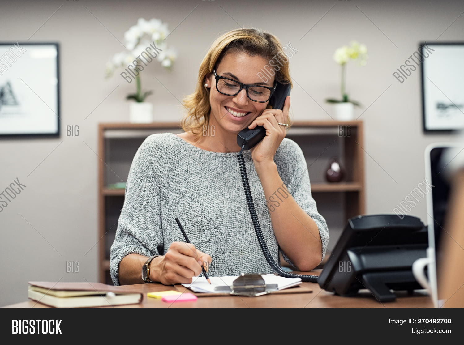 Beautiful mature woman talking on phone at creative office. Happy smiling businesswoman answering te