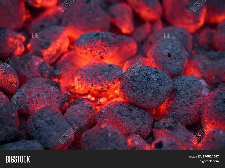 Coals smolder and glow. Residual flame from smoldering coals in cinder, closeup view. Flicker of bur