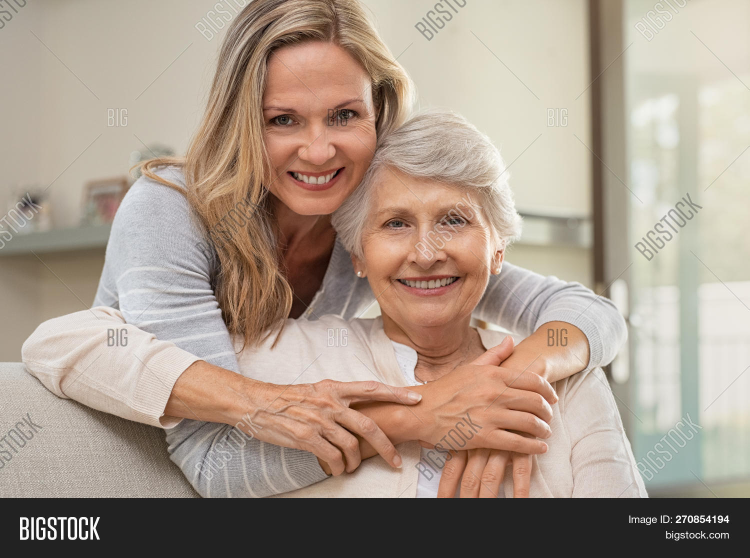 Cheerful mature woman embracing senior mother at home and looking at camera. Portrait of elderly mot