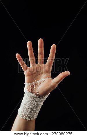 wrist wrapped with healing bandage, isolated on black stock photo