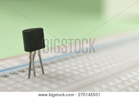 A NPN bc239 transistor connected to a breadboard on green background stock photo