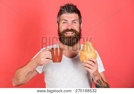But first coffee. Enjoy every sip of coffee. Bearded hipster enjoy breakfast drink coffee. Gastronomic pleasure. Man start morning with cup of coffee and fresh croissant. Morning tradition concept stock photo