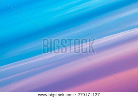 Varicolored striped surreal sky with shades of blue, cyan, cobalt, pink, purple, magenta colors. Diagonal lines of smooth clouds. Atmospheric background image of tender sky. stock photo