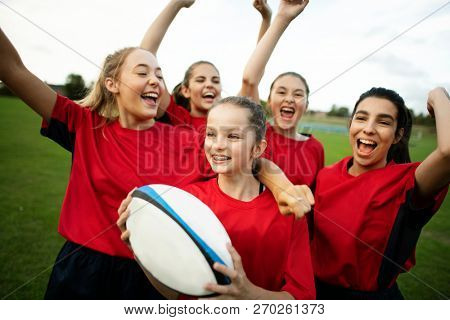 Energetic female rugby players celebrating stock photo