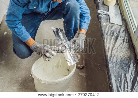master is applying white putty on a wall and smearing by putty knife in a room of renovating house in daytime stock photo