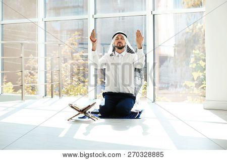 Muslim man with Koran praying on rug indoors stock photo
