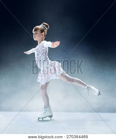 Little girl figure skating at the indoor ice arena. The dance, sport, winter, exercise, training, childhood, champion concept stock photo