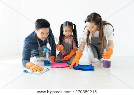 Happy young Asian family of three cleaning their home living room at weekend.Cute little helper. Family housework and household concept. stock photo