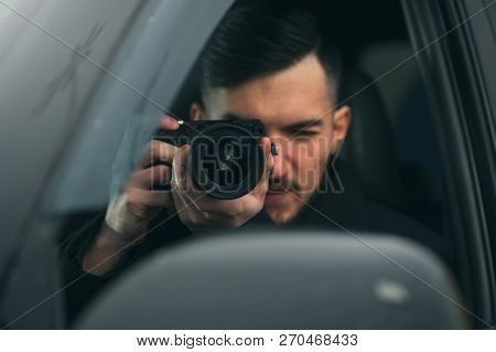 Young Male Spy Sits In The Car Taking Photos To The Camera With A Zoom Lens. Detective Agency Concept stock photo