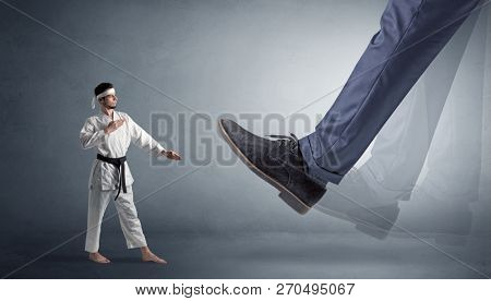 Big foot treading small young karate man stock photo