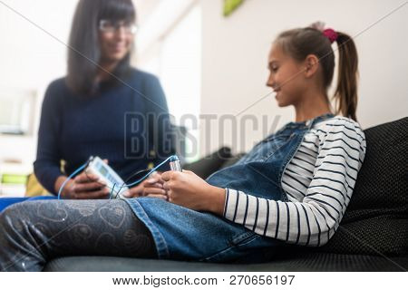 Female bioresonance therapist with her young girl client holding zapper electrodes. stock photo