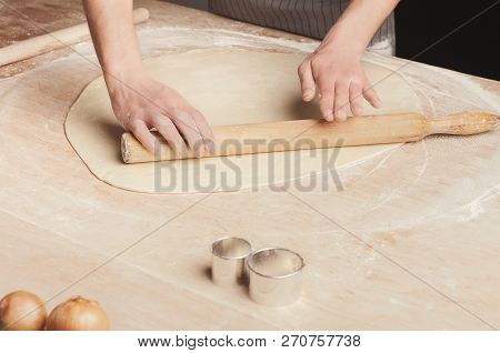 Making traditional Russian dumplings. Chef hands rolling out unleavened dough on kitchen table, cooking ingredients, copy space stock photo