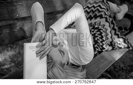 Try to remember. Boring literature. Woman tired face take break relaxing in garden reading book. Girl lay bench relax with book green nature background. Lady student read boring literature outdoors stock photo