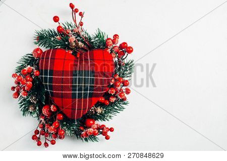 Christmas decorative wreath of holly, ivy, mistletoe, cedar and leyland leaf sprigs with red berries over white background stock photo