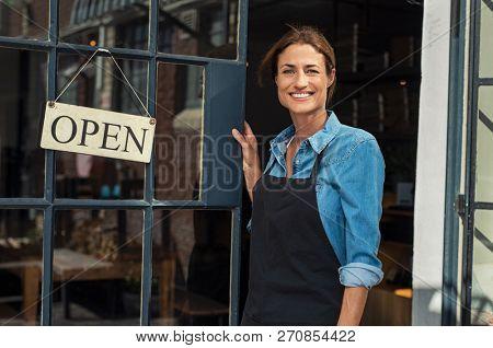 Portrait of a happy waitress standing at restaurant entrance. Portrait of mature business womanatten