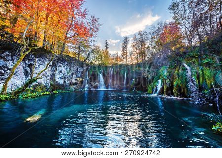 Amazing waterfall with pure blue water in Plitvice lakes. Orange autumn forest on background. Plitvice National Park, Croatia. Landscape photography stock photo