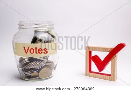 Glass jar with coins and the words Votes and a checkbox. Concept of voting for money. Bribing voters. Corruption in the electoral system. Interference in the election. Lobbying. stock photo