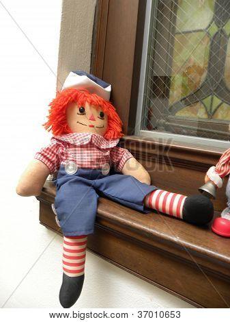 Raggedy Andy doll sitting on a windowsill. stock photo