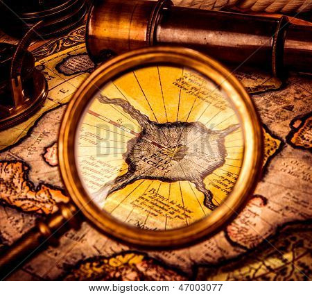 Vintage magnifying glass lies on the ancient map of the North Pole (also Hyperborea). Arctic continent on the Gerardus Mercator map of 1595. stock photo