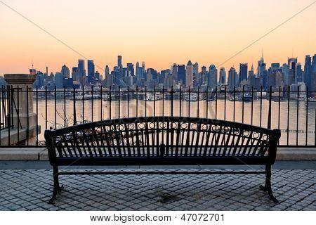 Banc dans le parc et la ville de new york midtown manhattan au coucher du soleil avec vue panoramique skyline sur hudson r