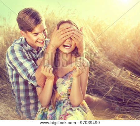 Beauty Couple relaxing on wheat field together. Teenage girlfriend and boyfriend having fun outdoors