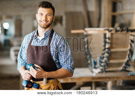 Waist-up portrait of smiling bearded craftsman with electric drill in hands standing in spacious workshop and looking at camera stock photo