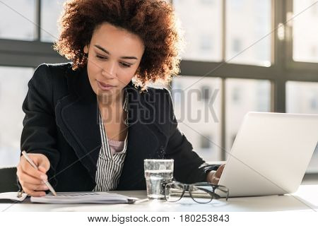 Portrait of African American female expert analyzing printed business report while sitting at desk i