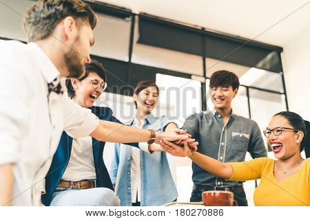 Multiethnic diverse group of happy colleagues join hands together. Creative team casual business coworker or college students in project meeting at modern office. Startup or teamwork concept