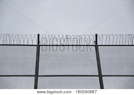 Barber wire concertinas in a border and a blue cloudy sky. Immigration and prison concept. Empty copy space for Editor's text. stock photo