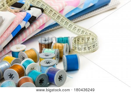 cotton fabric material tailor measurement tape with spools of thread cotton stock photo