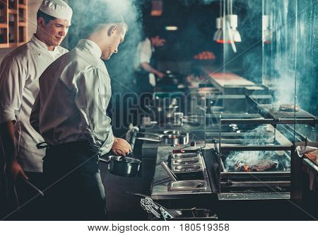 Food concept. Chef in white uniform monitors the degree of roasting and greases meat with oil in sau