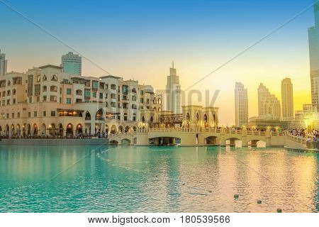 Scenic view of Burj Khalifa Lake, a pool where they dance the Dubai Fountain. On background, the bridge that connects the Dubai Mall to Souk Al Bahar. People crowd around the shopping area at sunset. stock photo