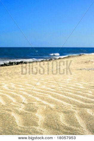 Rippled sand on a golden sandy beach with vast blue,cloudless sky. stock photo
