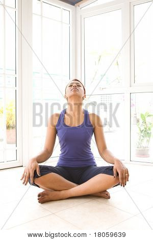 Young Asian female doing neck stretching exercise to release build up tension. stock photo