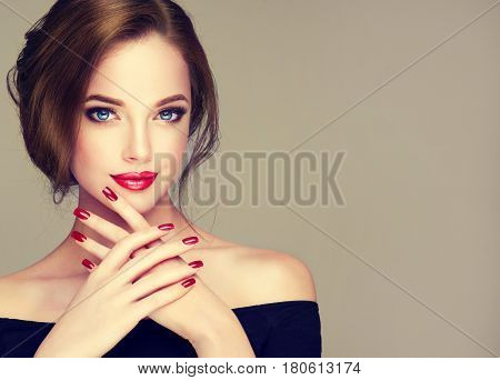 Beautiful model girl with elegant hairstyle . Woman with red lips and nails  . Cosmetics, beauty and manicure on nails