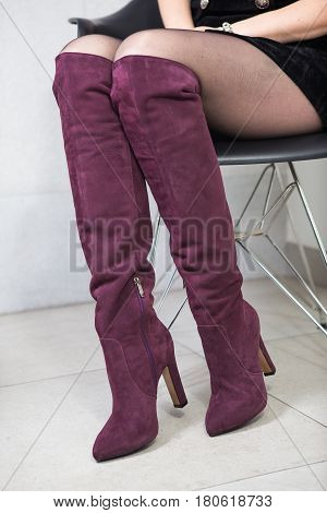 girl in high red boots a coat in the office. lookbook women's high leather boots stock photo