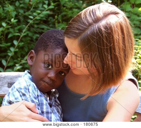 young caucasian woman holding a young african american child. stock photo
