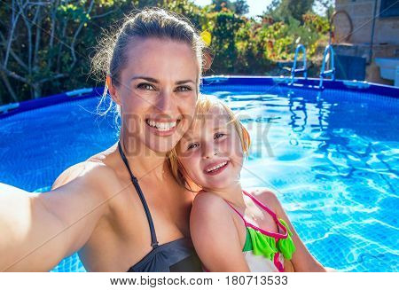 Fun weekend alfresco. smiling active mother and daughter in beachwear in the swimming pool taking selfie stock photo