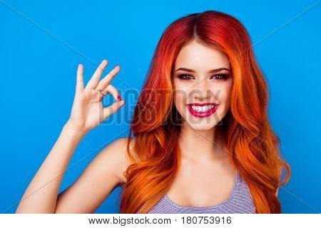 Close-up portrait of cute attractive excited girl with long ginger fair hair showing okay sign with fingers while standing on blue background stock photo