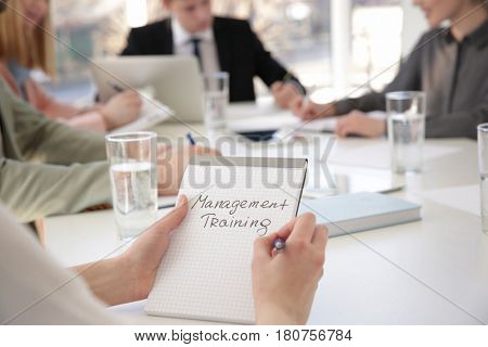 Woman holding notebook with text MANAGEMENT TRAINING at business presentation stock photo