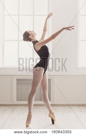 Classical Ballet, ballerina on pointe. Beautiful graceful dancer practice ballet positions near large window in white light hall. Training, high-key soft toning.