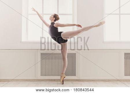 Classical Ballet dancer in arabesque position in light hall. Ballerina training, high-key soft toning.