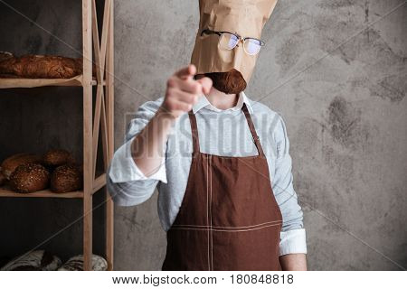 Image of young man baker standing with paper bag on head wearing glasses at bakery near bread. Pointing at camera. stock photo